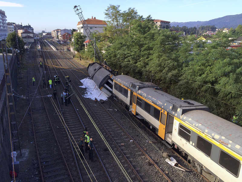 epa05531352 Spanish emergency services members and Civil Guard officers work at the site where a train derailed near O Porrino in Pontevedra, resulting in the death of at least two people and several others injured, in the northwestern province of Galicia, Spain, 09 September 2016. The train covering the Vigo-Oporto (Portugal) route was carrying some 60 passengers when one of its three coaches overturned provoking the accident. Spanish rail service Renfe has confirmed that at least two people were dead and a large number injured, some of them serious. Renfe also said that the train belongs to Portuguese company Comboios and that the engine driver has Portuguese citizenship.  EPA/SALVADOR SAS