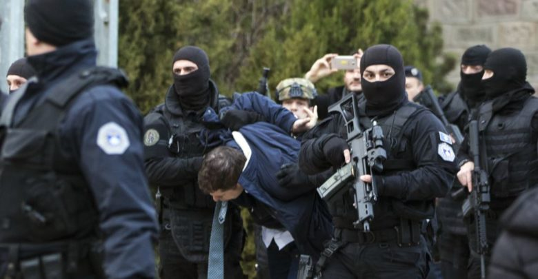 Kosovo police escort Marko Djuric a Serb official to a police station in Kosovo capital Pristina after he was arrested in northern Kosovo town of Mitrovica on Monday, March 26, 2018. Kosovo police arrested a Serb official after he was banned from visiting a divided town in northern Kosovo and then fired tear gas and stun grenades at Serb protesters Monday. (AP Photo/Visar Kryeziu)